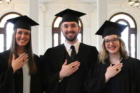 three students celebrate Ring Day around a cake