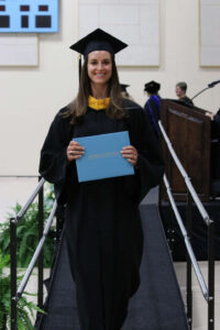 Kinon walking down from the stage holding her degree