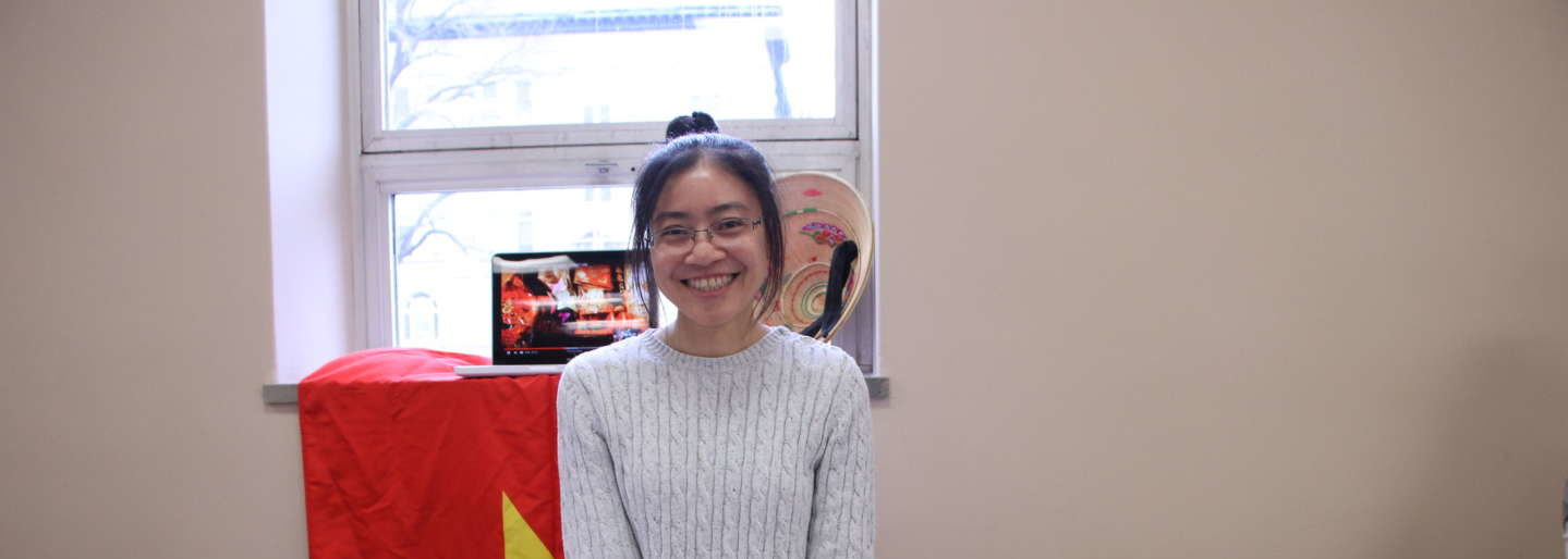 Vietnamese student standing at booth during International Week event