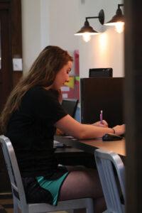 Emma sitting at the computer bar.