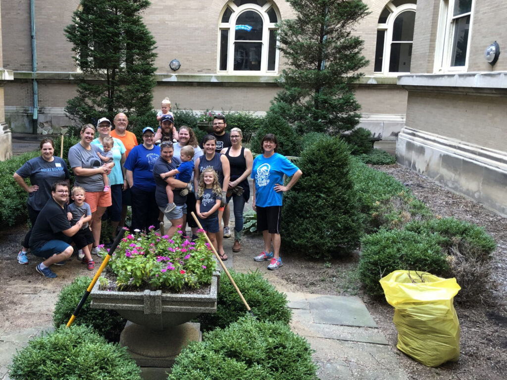 Group of alums standing in the Guerin Courtyard during service project