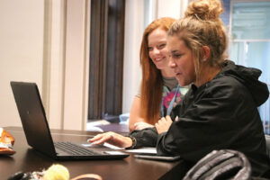 Two students studying on a laptop.