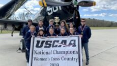 The women's cross country team holding their champions banner