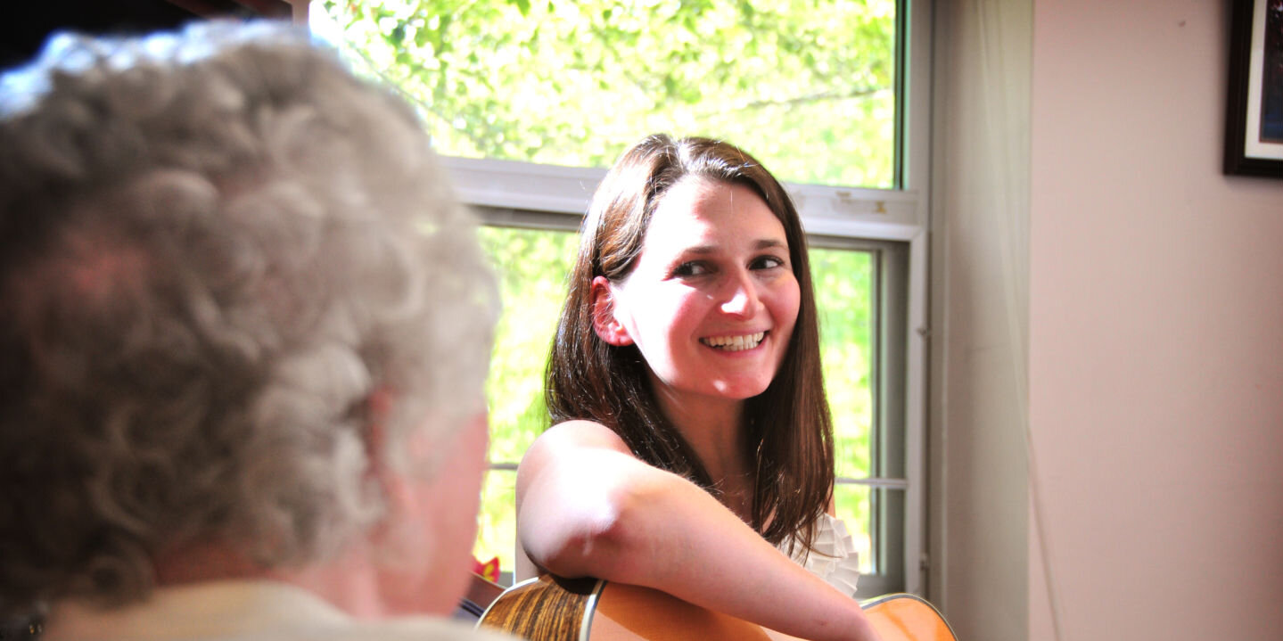 Music therapy student playing guitar for a senior