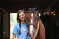 Smiling equine student holding the head of their horse