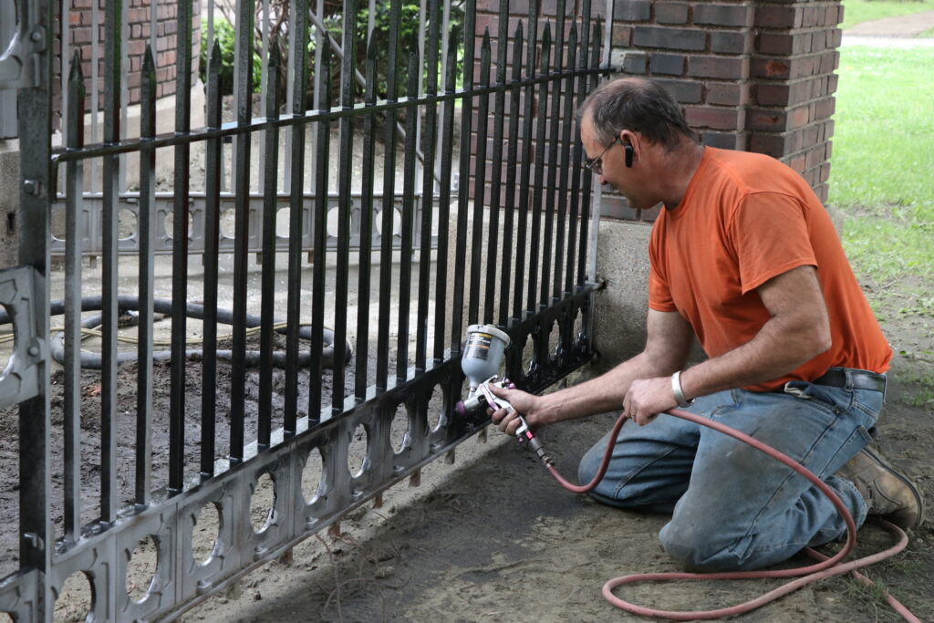 Worker painting the gates