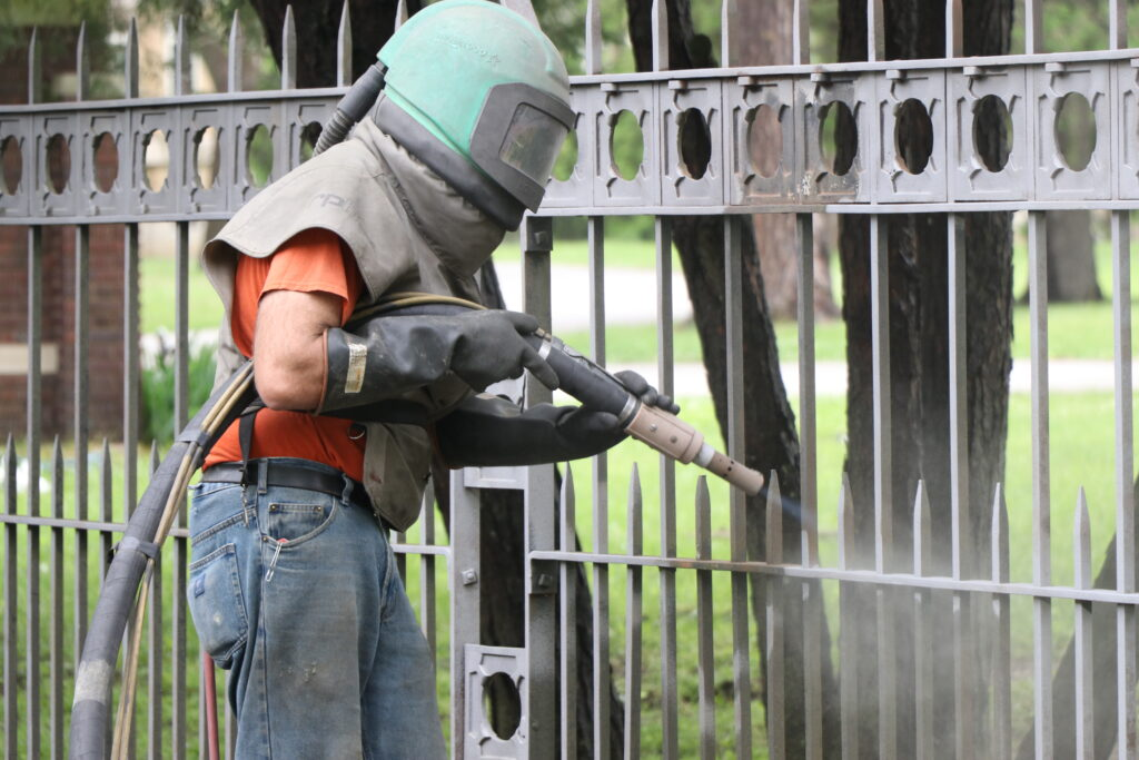 Worker sandblasting the gates