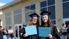Graduates hold up their diplomas after the 2020 commencement