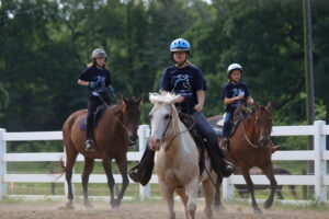 Campers ride their horses
