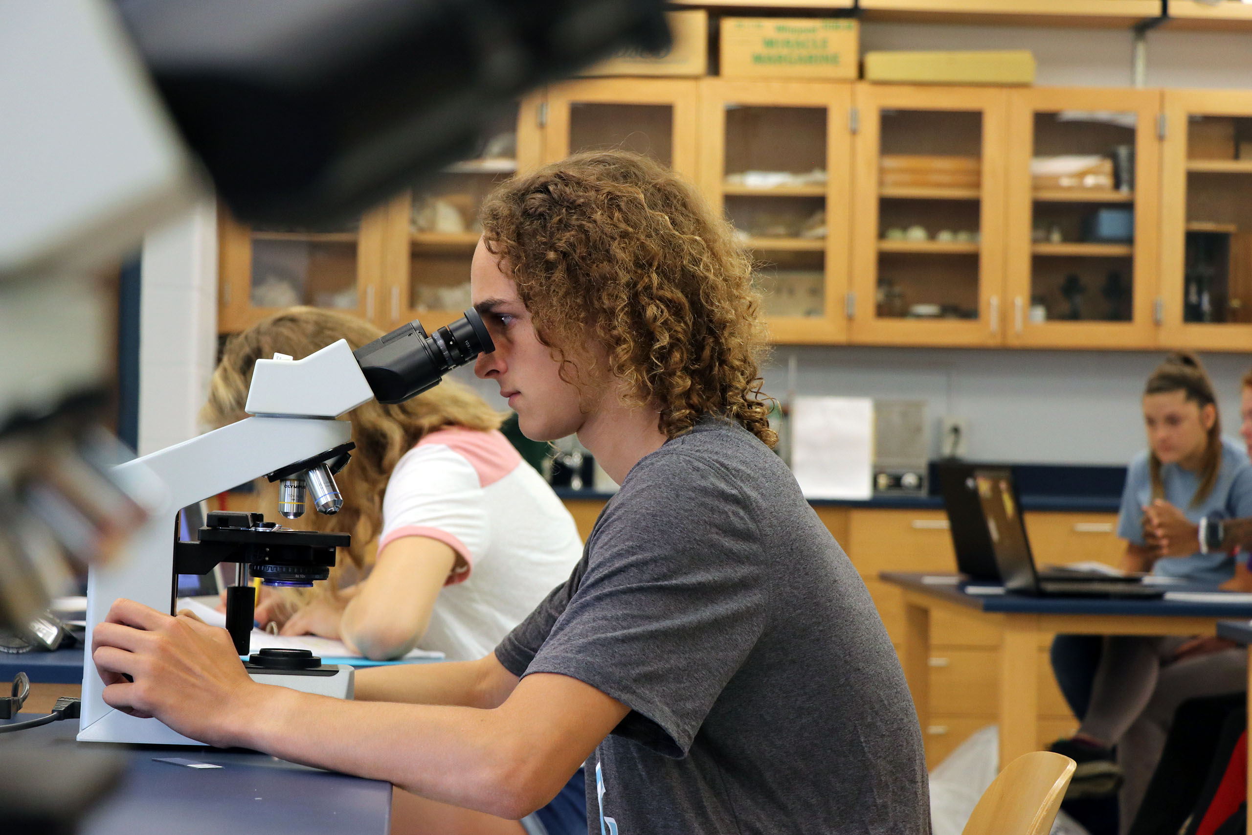 Student looking into a microscope during science class.