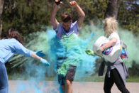 Student running through cloud of color