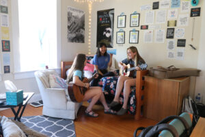 Students playing guitars together in a dorm room