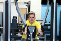 A student working out on a machine in Club 64