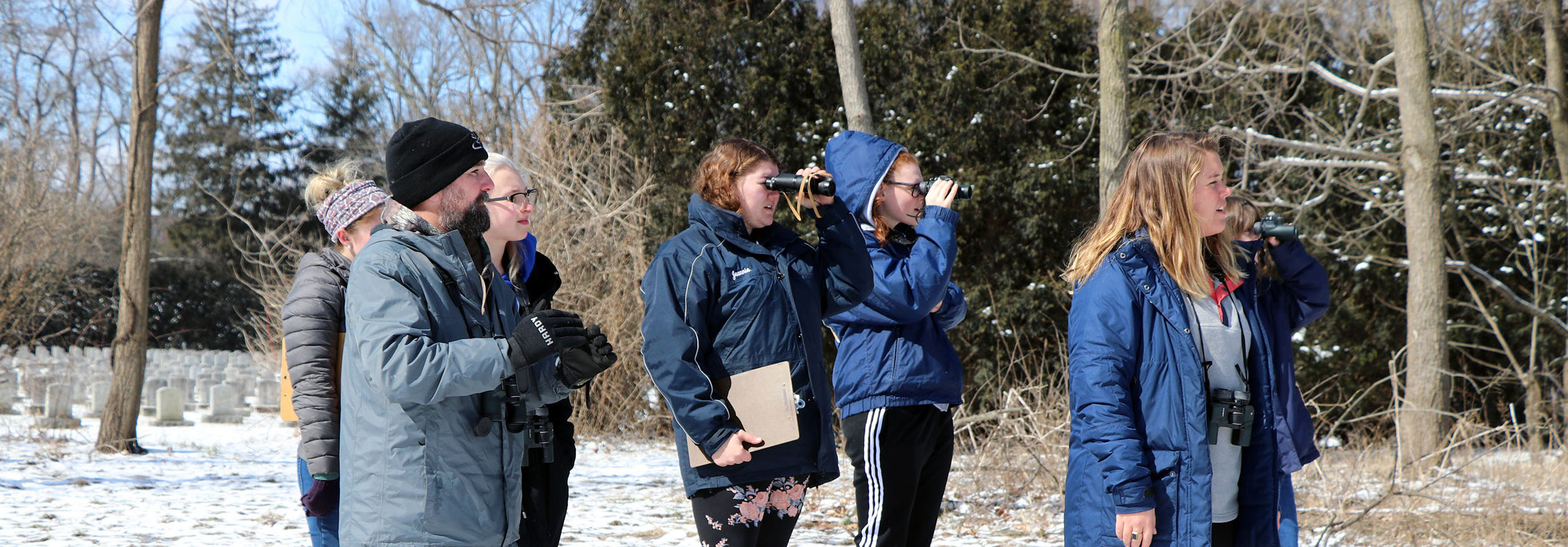 Students and instructor standing outside looking through binoculars
