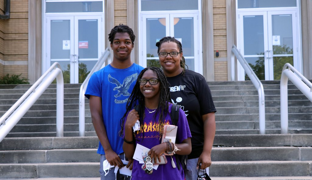 Family stands together in front of Le Fer Hall