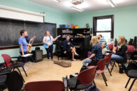 A music class with two people playing guitars, a student singing, and four students listening
