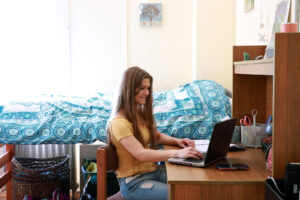 A student working on a computer in a dorm room