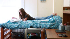 A student laying on a bed studying in a dorm room