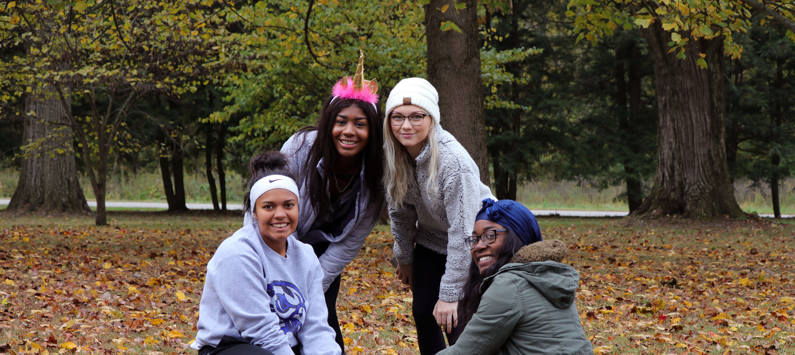 Diverse group of students show off a newly planted tree