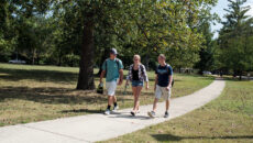 Students walking down a sidewalk on campus