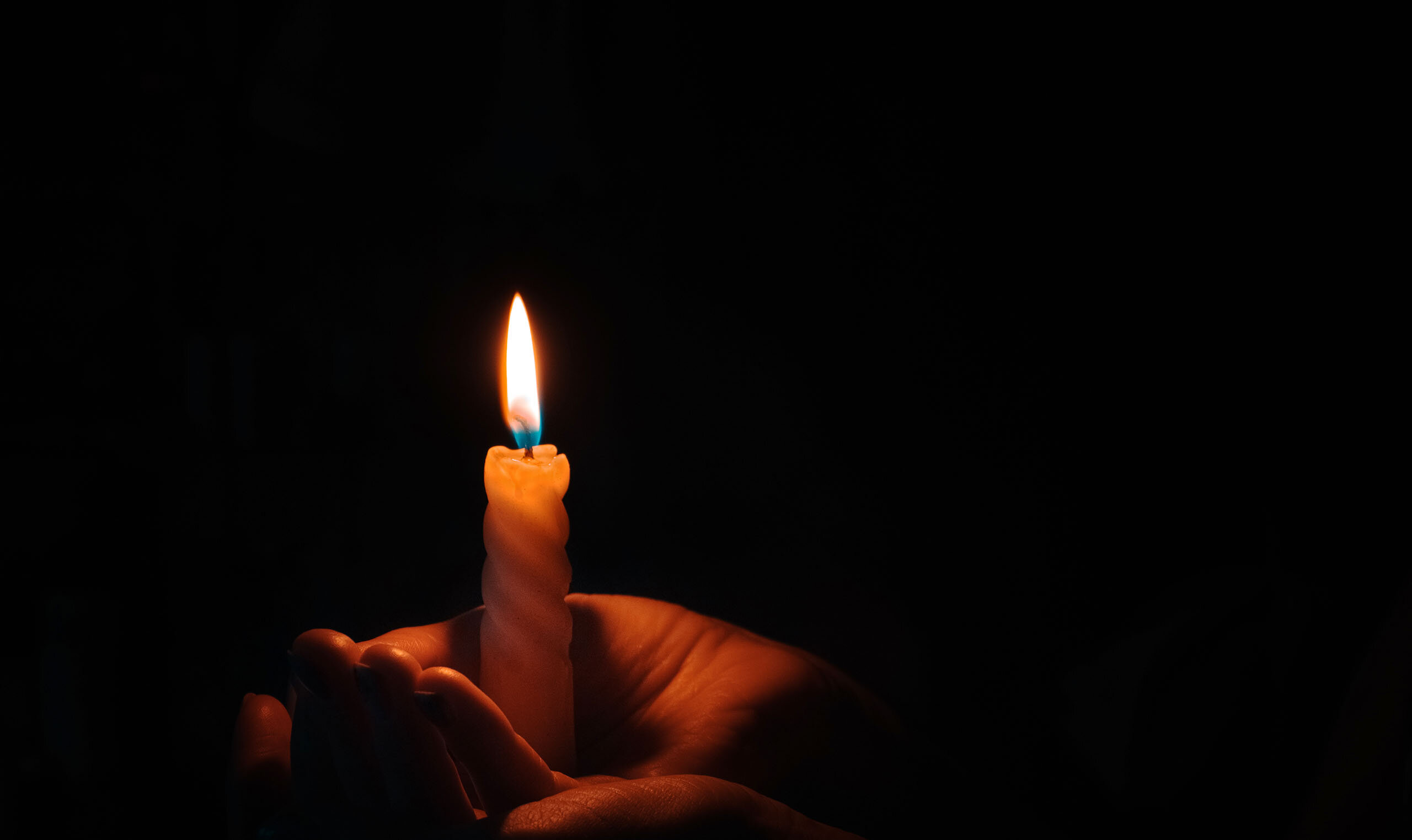 Hands holding candle