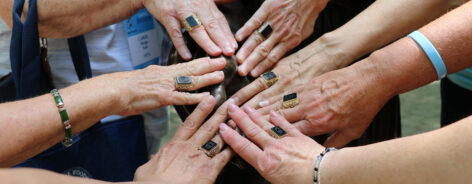 Alums putting their hands together with Woods Rings at Reunion