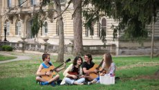 students on the lawn playing music together