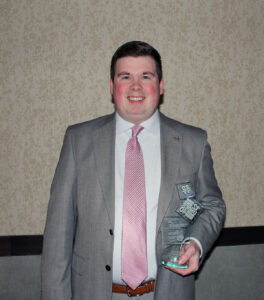 AJ Dinkel holding his top 12 under 40 award