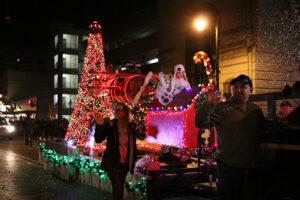 Parade float covered in lights with lifesize toy airplane on top