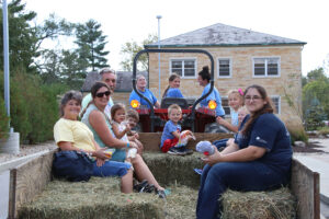 Group of alumni riding on tractor and hay-filled trailer
