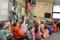 Class of elementary students raising hands to answer a question