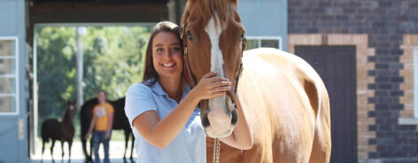 Equine student standing with their horse in front of the stables