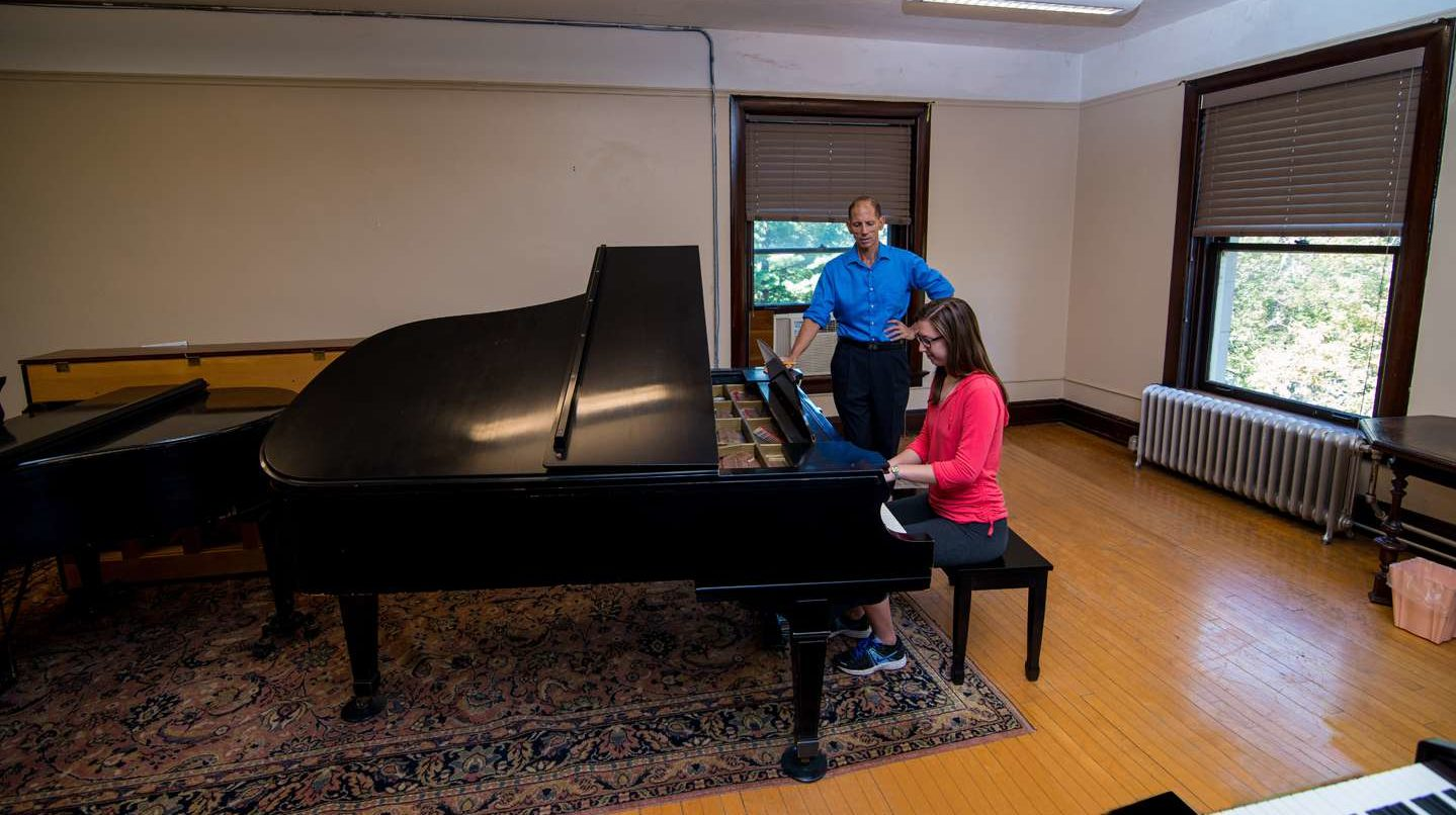 Student playing piano with professor watching