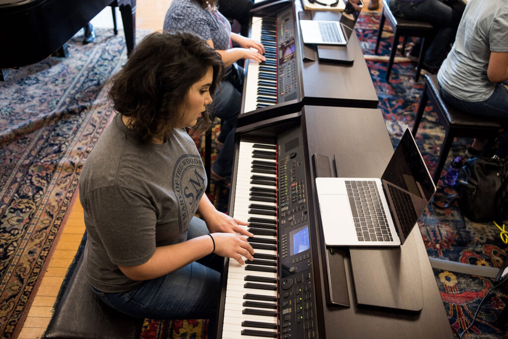 Music student playing piano in classroom
