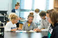 Students working with professor in Chemistry lab