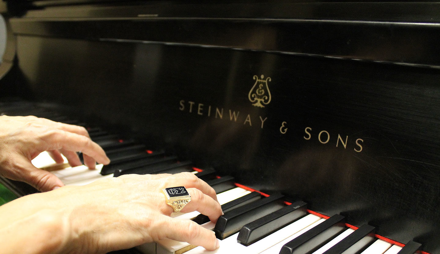 Hands wearing Woods ring playing Steinway piano