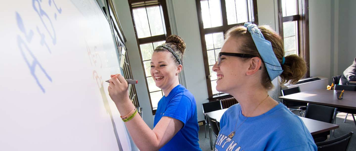Two female students standing at a dry erase board working together on homework.