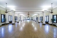 The beautiful, large Le Fer Hall Ballroom with the chandeliers, columns and wood floors.