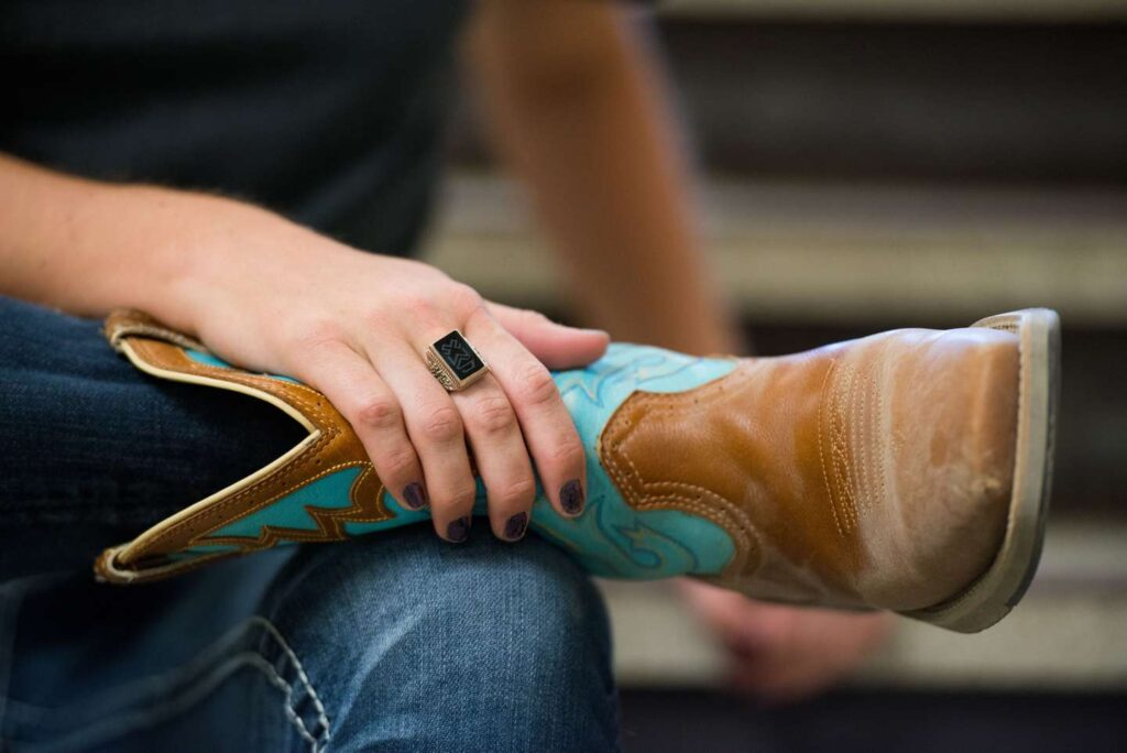 A close-up of an equine student's cowboy boot with her hand and Woods Ring holding onto it.