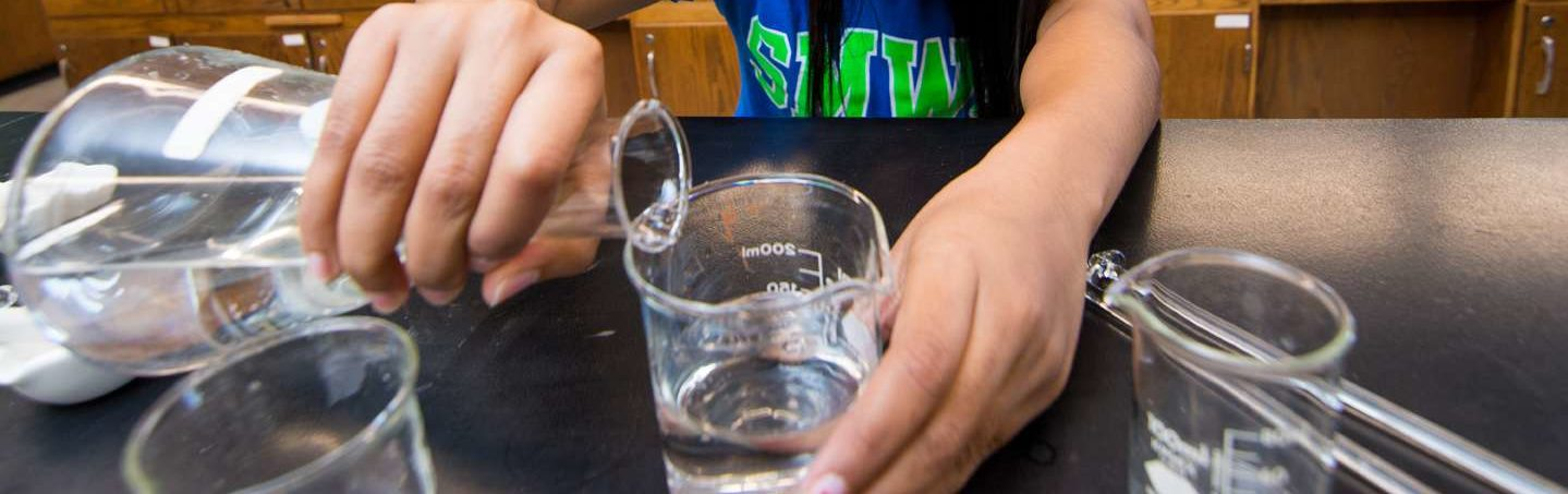 Someone's hands on a chemistry beaker pouring liquid into a glass.
