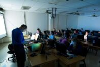 A computer classroom with low light as an instructor teaches.
