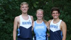 Two male and one female cross country students stand together smiling.