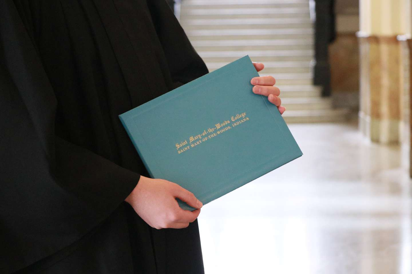 The hands of someone in a graduation gown holding a degree jacket that says Saint Mary-of-the-Woods College.