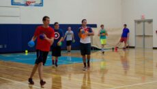 Male students holding colorful balls playing dodge ball in the Knoerle Center.