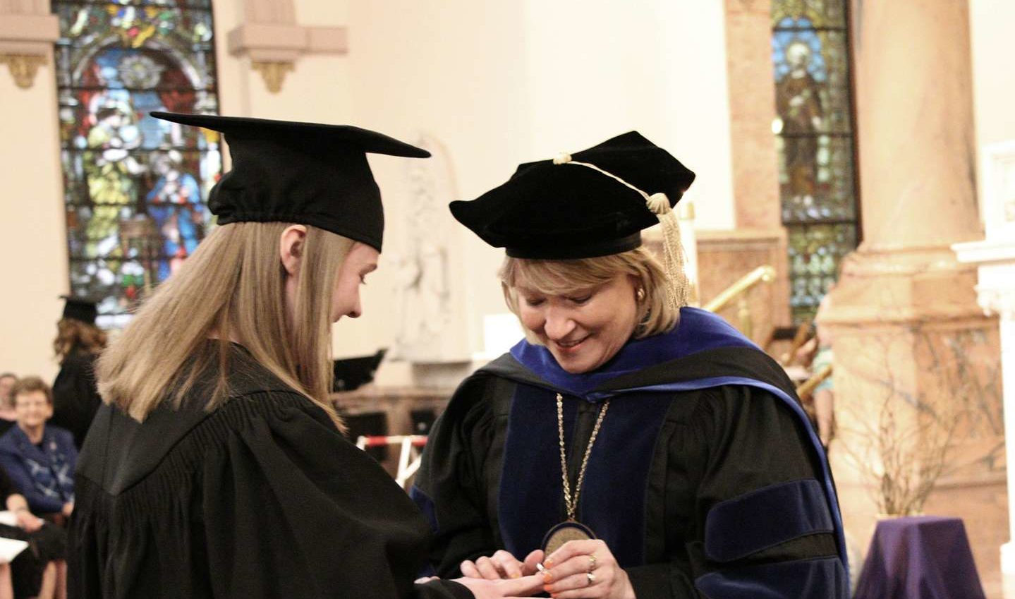 President Dottie King puts a Woods Ring on a student's finger.
