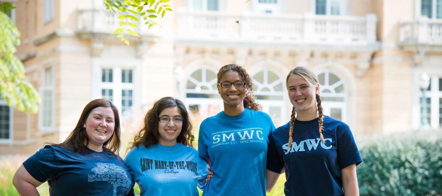 Four female student with arms linked and SMWC t-shirts smiling.