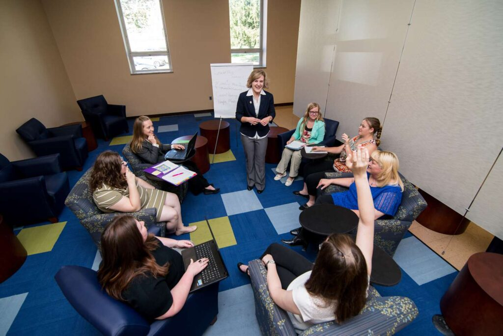 A group of female students in a circle having a business meeting.