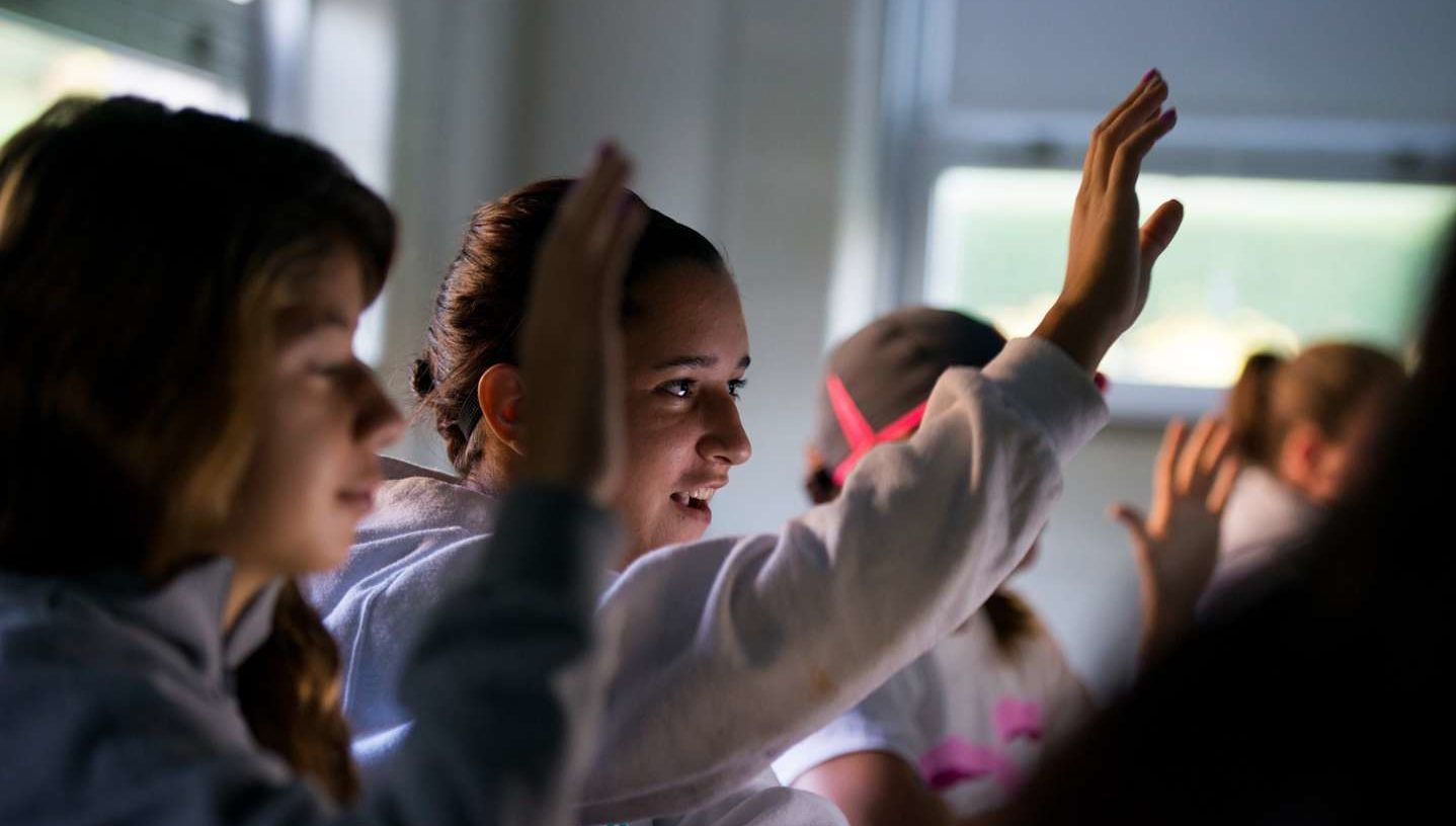 Students hold up their hands in a classroom.