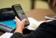 The hand of a student holding a graphing calculator and working on an assignment.