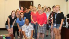 A group of SMWC students smiling with President Dottie King in her office.